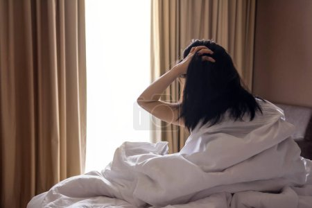 Photo for A Lazy Woman with Messy Hair sitting on White Bed and Looking Outside Through Window in the Morning, after Woke Up - Royalty Free Image