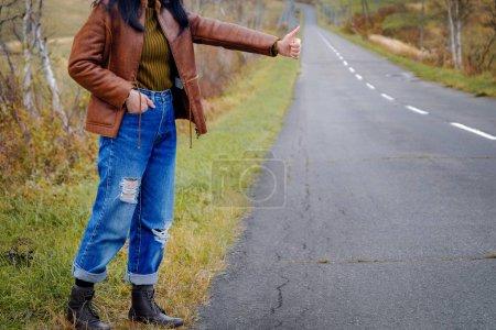 Photo pour Les déplacements et le Concept de liberté. Jeune auto-stoppeur voyageur femme se tenant debout sur le bord de la route - image libre de droit