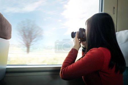 Photo pour Concept de voyage. Jeune femme de voyager avec caméra prenant des photos tout en étant assis dans le Train - image libre de droit