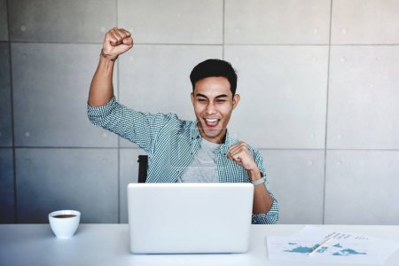 Photo pour Small Business and Successful Concept. Jeune homme d'affaires asiatique heureux de recevoir une bonne nouvelle ou des profits élevés de l'ordinateur portable, Propre entreprise atteint les objectifs. Levons les armes pour célébrer le succès - image libre de droit