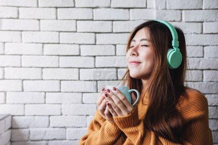 Photo pour Jeune femme écoute musique de casque dans la maison confortable, les yeux fermés et relaxant en moment de bonheur - image libre de droit