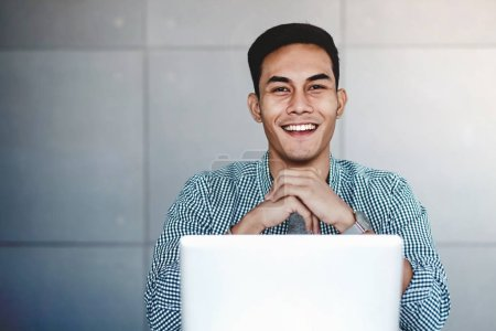 Photo for Happy Young Asian Businessman Working on Computer Laptop at  his Workplace. Hands on Chin, Smiling and looking at Camera - Royalty Free Image