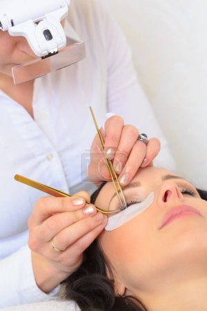 closeup of a female face by receiving of eyelash lengthening at the beauty salon