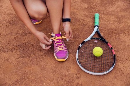 Photo for Close-up view of active woman getting ready for playing a game of tennis, tying shoelaces. Racket and ball are on the court. Outdoors. - Royalty Free Image