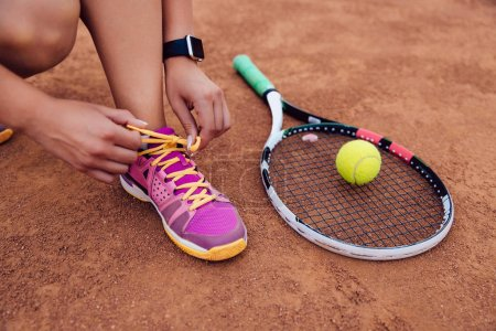 Photo for Athlete woman getting ready for playing a game of tennis, tying shoelaces. Close-up view of racket and ball. - Royalty Free Image