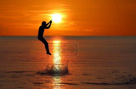 Photo pour L'homme a sauté de la mer près de la plage au coucher du soleil fond du ciel rouge - image libre de droit