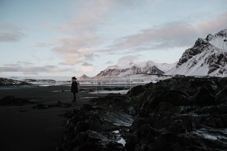 A person standing on a black sand beach in front of a snowy landscape in Stokksnes, Iceland