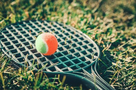 Photo for Tennis ball lying on a racket in the green grass. Summer background. Outdoor summer games concept. - Royalty Free Image