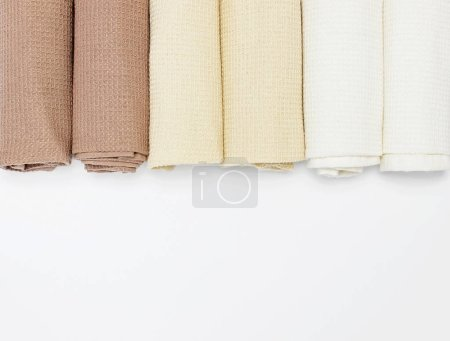 Multicolored clean towels on a white background top view with copy space. Texture of cotton, waffle towel, textiles. Towels for kitchen or Spa concept. Isolated object