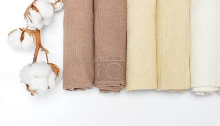 Multicolored clean towels with a branch of cotton on a white background top view with copy space. Texture of cotton, waffle towel, textiles. Towels for kitchen or Spa concept. Isolated object