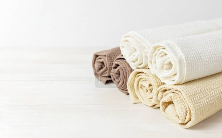 Multicolored clean towels on a light wooden background with copy space. Texture of cotton, waffle towel, textiles. Towels for kitchen or Spa concept. Isolated object