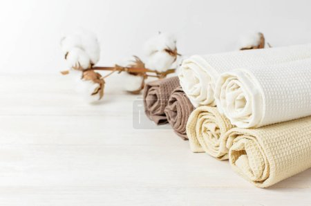 Multicolored clean towels with a branch of cotton on a light wooden background with copy space. Texture of cotton, waffle towel, textiles. Towels for kitchen or Spa concept. Isolated object