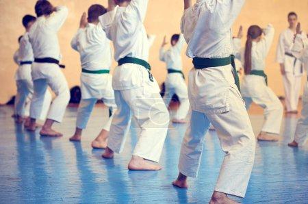 Kinder beim Karate-Do-Training. junge Athleten in traditionell weißen Kimonos mit farbigen Gürteln. Banner mit Platz für Text. Retro-Stil. für Webseiten oder Werbedrucke. Foto ohne Gesichter.