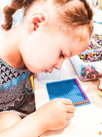 Little girl working on craft project with colorful beeds.
