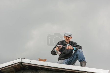 Photo pour Un homme en tenue de travail serre les vis avec un tournevis sur le toit contre un ciel nuageux . - image libre de droit
