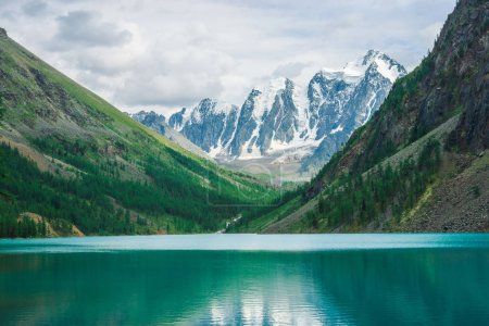 Photo for Shine water in mountain lake in highlands. Wonderful giant snowy mountains. Creek flows from glacier. White clear snow on ridge. Amazing atmospheric landscape of majestic Altai nature. - Royalty Free Image