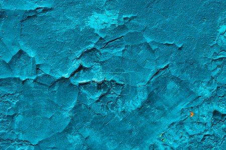 Imperfect concrete surface. Cracked blue paint clo...