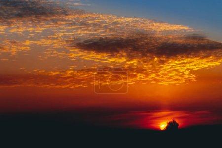 Photo pour Brillance ensoleillée sur les nuages. Merveilleuse aube vive. Beau coucher de soleil orange calme. Lever de soleil surréaliste scénique. Incroyable ciel nuageux bleu rouge. Coucher de soleil pittoresque. Paysage nuageux atmosphérique. Cercle de soleil au-dessus de l'horizon - image libre de droit