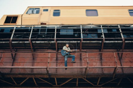 Photo for Bluesman with acoustic guitar on railroad bridge - Royalty Free Image