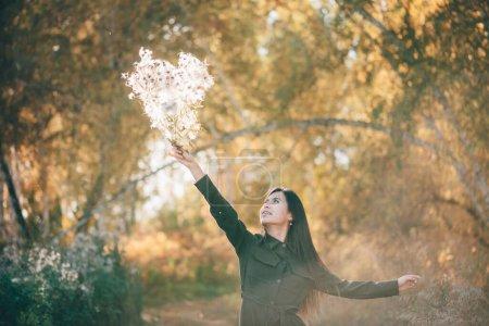 Photo pour Belle fille rêveuse avec bouquet de fleurs de chardon en lumière du soleil dorée sur fond bokeh avec des feuilles jaunes. Fille inspirée aime coucher de soleil dans la forêt d'automne. Portrait de beauté féminine parmi le feuillage d'automne . - image libre de droit