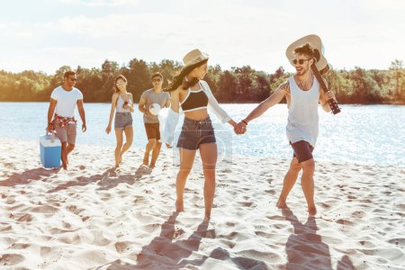 smiling multiethnic friends with ball and acoustic guitar walking on sandy beach