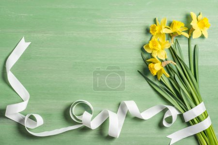 Photo for View from above of bouquet of daffodils wrapped by white ribbon on green background - Royalty Free Image
