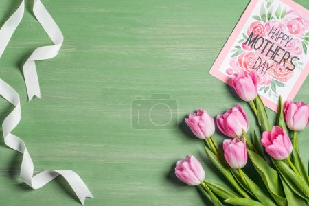 elevated view of white ribbon, bouquet of pink tulips and card with lettering happy mothers day on green background