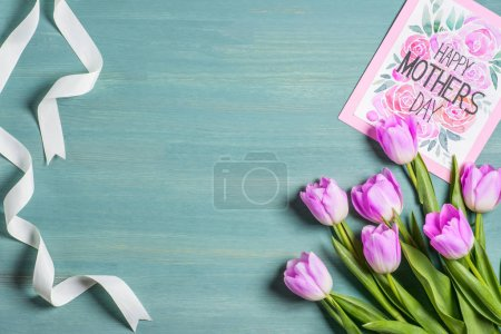 top view of white ribbon, bouquet of tulips and card with lettering happy mothers day on blue background
