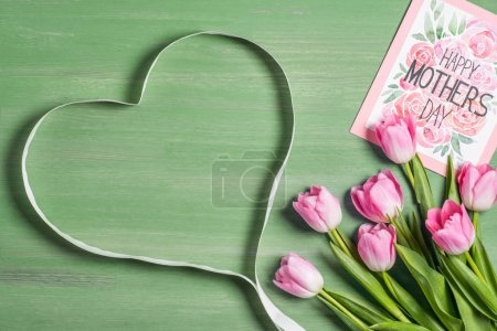 elevated view of heart symbol made from ribbon, bouquet of tulips and card with lettering happy mothers day on green background