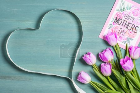 top view of heart symbol made from ribbon, bouquet of tulips and card with lettering happy mothers day on blue background