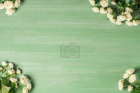 Photo pour Vue surélevée des bouquets de roses blanches sur fond vert - image libre de droit