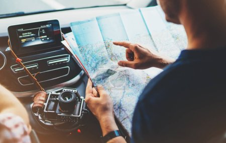 Hipster man looking and point finger on location navigation map in car, tourist traveler driving and hold in male hands europe cartography, view and plan tourist way road, trip in transportation from window auto
