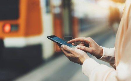 Photo pour Hipster de Blogger en utilisant en mains gadget mobile téléphone, message texto femme sur smartphone écran vide, message SMS, concept de maquette en ligne wifi internet hipster en attente sur le quai de la gare train de fond - image libre de droit