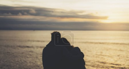 Couple hugging on background beach ocean sunrise, meeting of lovers concept, silhouette two romantic people cuddling and looking on view evening seascape, hipster enjoy sunset together, travel holidays vacation relax