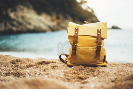 Hipster swimming mask on background blue sea ocean horizon, hiker tourist yellow backpack on sand beach, blurred panoramic seascape blank, traveler relax holiday concept, sunlight view in trip vacation