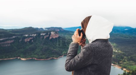 photographer tourist traveler standing on green top on mountain holding in hands digital photo camera, hiker view from back taking photography, girl enjoy nature panoramic landscape in trip, relax holiday hobby concept