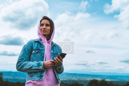 Tourist young girl on background blue sky using mo...