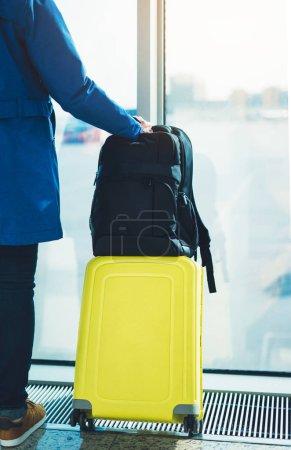 Photo pour Touriste avec sac à dos valise jaune est debout à l'aéroport sur fond grande fenêtre, voyageur personne attend dans le salon de départ hall du concept de voyage de vacances terminal hall de l'aéroport - image libre de droit