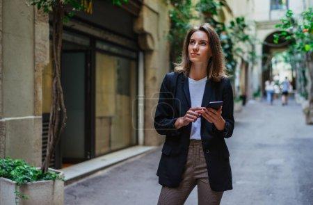 Photo pour Femme d'affaires réservant un hôtel lors d'un voyage d'affaires utilisant les technologies Internet son téléphone portable, une touriste tenant entre les mains un smartphone voyage de planification dans la vieille ville d'Europe - image libre de droit