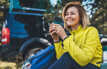 Photo for Girl smiles and enjoys breakfast outdoors summer nature, tourist hold hand mug of warm tea during recreation trip, happy hiker laughing showing teeth drink coffee from thermos in green forest. Happy tourist relax while traveling auto - Royalty Free Image