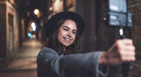Photo pour Voyageur blogueuse tournage vidéo pour les médias sociaux avec appareil photo numérique. Souriant jeune femme vlogger prendre selfie vidéo sur la lumière nuit ville - image libre de droit