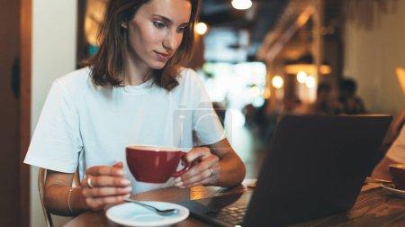 Photo pour Femme gestionnaire tenant dans les mains tasse de café à l'aide d'un ordinateur portable dans le café, fille pigiste regarde moniteur tout en se relaxant avec cappuccino, femme d'affaires travaillant via ordinateur portable dans le restaurant et la communication en ligne - image libre de droit