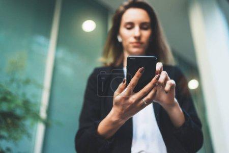 Photo pour Gros plan des mains féminines tenant un smartphone le soir dans la rue, femme d'affaires concentrée en costume noir et utilisant un smartphone moderne près du bureau tôt le matin - image libre de droit