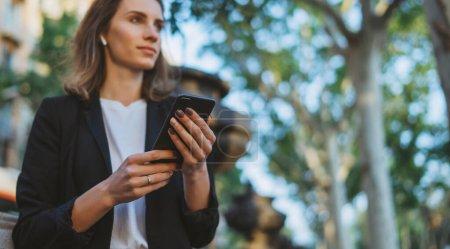 Photo pour Jeune femme d'affaires écrit des messages sur smartphone tout en marchant dans un parc de Barcelone le jour ensoleillé, fille financière professionnelle utilise la technologie Internet sur l'appareil mobile à l'extérieur - image libre de droit