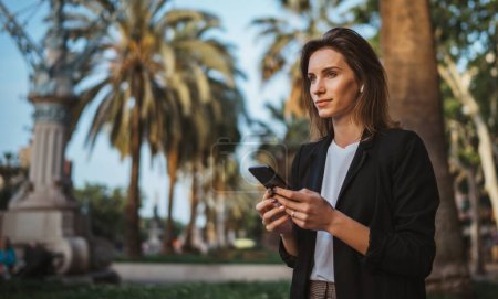 Photo pour Femme marchant et bavardant avec le directeur de bureau à l'extérieur dans le parc de la ville de Barcelone, femme d'affaires réussie tapant sur l'écran tactile du téléphone portable tandis que la technologie Internet en plein air - image libre de droit