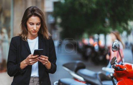 Photo pour Succès femme en costume d'affaires tient le vendeur dans la main paie pour la location de scooter application en ligne pour le voyage autour de Barcelone, hipster féminin regarde la carte sur son téléphone mobile à louer cyclomoteur rouge pour un voyage rapide au travail, concept de transport urbain - image libre de droit