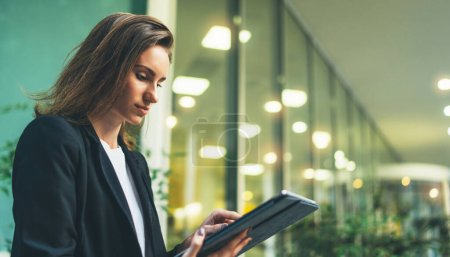 Photo for Young business woman chatting on touch pad with colleagues on social media office lighting lights in background, women's hands using tablet outdoors, lifestyle and communication concepts - Royalty Free Image