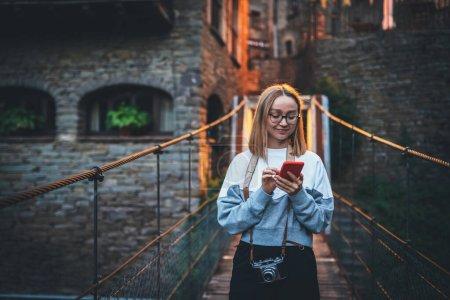 Photo pour Touriste fille blonde avec des lunettes utilise smartphone voyageant à travers la vieille ville historique Europe, les jeunes plans hipster marcher à travers les sites architecturaux de la vieille ville et regarde la carte dans le téléphone portable - image libre de droit