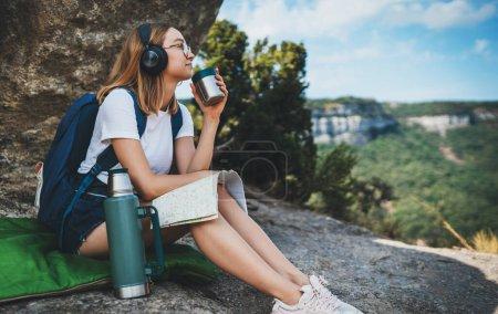 Photo pour Jeune fille voyageant en montagne itinéraire de planification sur la carte et boire du thé de thermos profiter du voyage, étudiante touriste avec des lunettes de détente dans la nature pendant les vacances écouter de la musique avec des écouteurs - image libre de droit