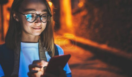 Photo for Close up portrait of young blonde girl with cellphone screen reflected in glasses using Internet technology device at night on city street against background of evening lights, empty copy space for your text - Royalty Free Image
